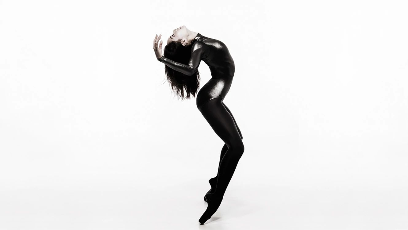 Female dancer in shiny black leotard with black tights in black pointe shoes in a backbend pose