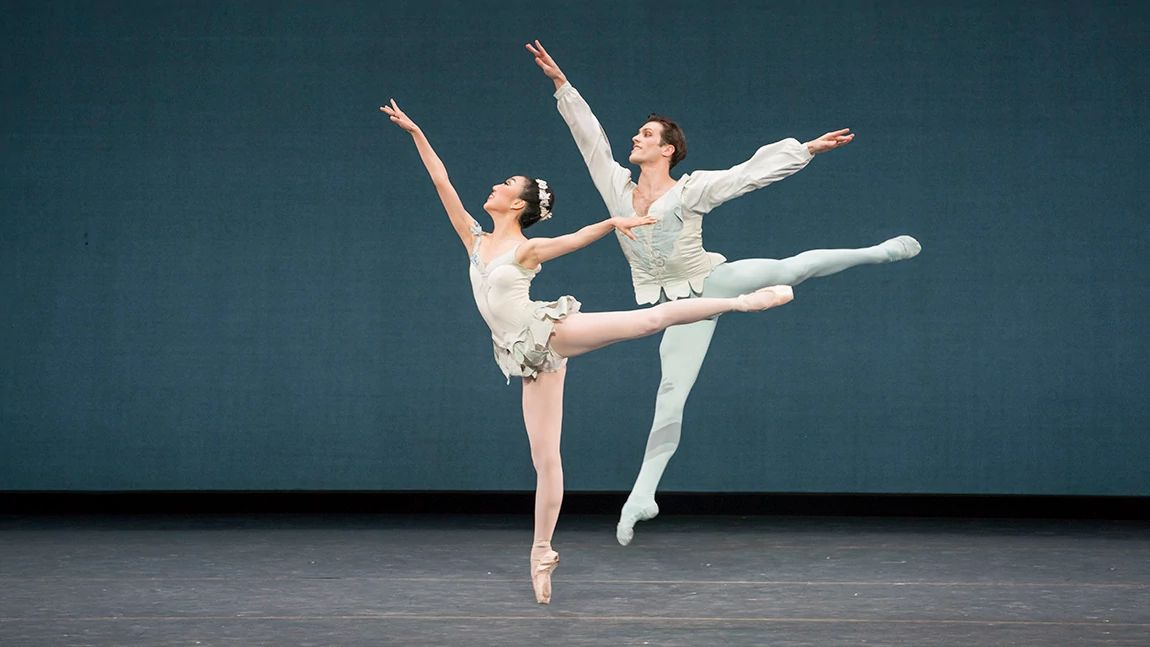 Male and female dancer leaping in white and light blue costumes