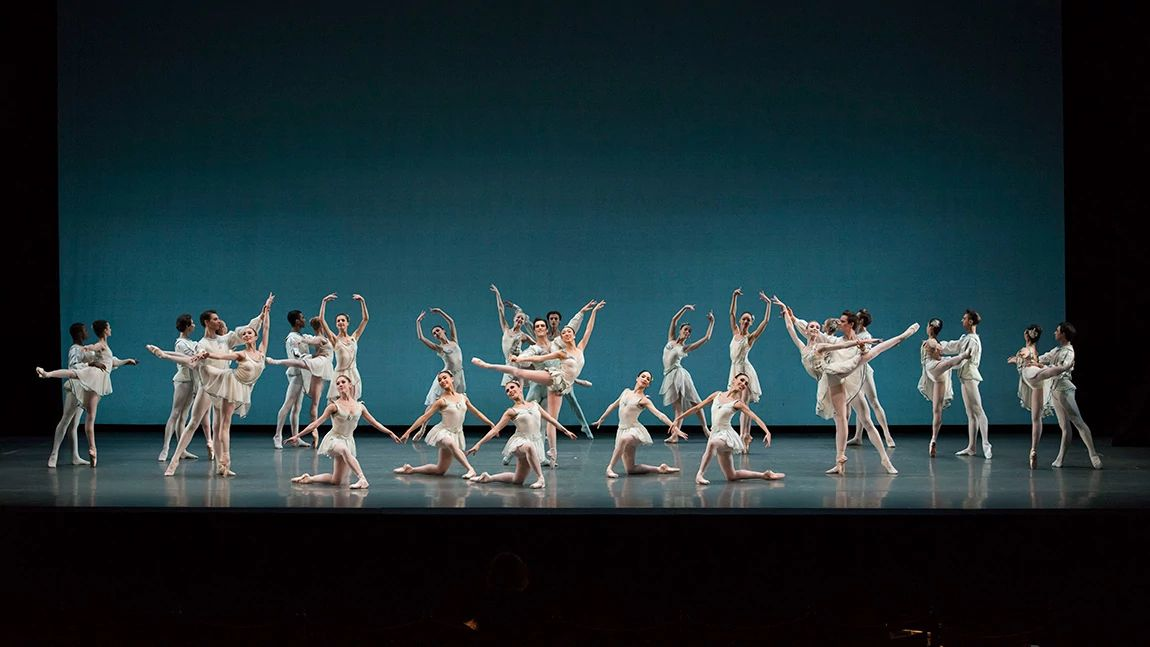 Group of posed dancers in white and light blue costumes